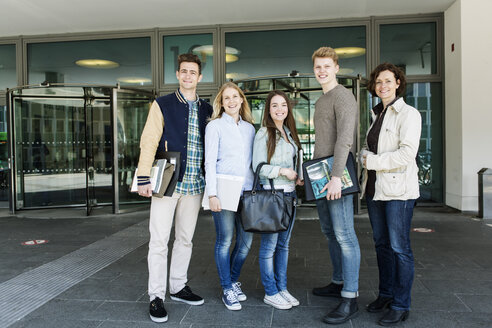 Portrait of happy students and professor standing at campus - MASF04067