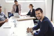 Portrait of happy young businessman with colleagues in background at conference room - MASF04079