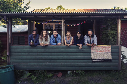 Portrait of happy multi-ethnic friends standing on porch at log cabin - MASF04082