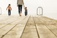 Rear view of family walking on pier against clear sky - MASF04088