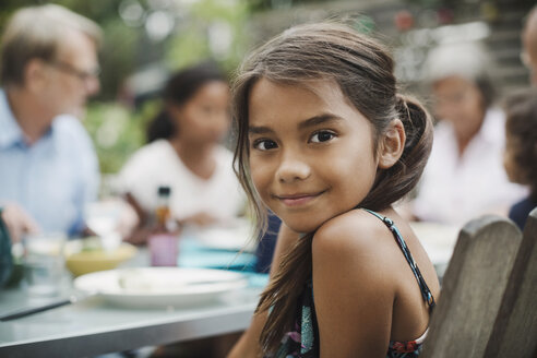 Portrait of smiling girl sitting with family at outdoor dining table - MASF04091