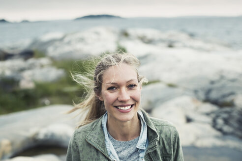 Portrait of happy young woman on rock by sea - MASF04094