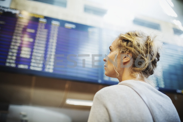 Rear view of businesswoman looking at arrival departure board in airport - MASF04100