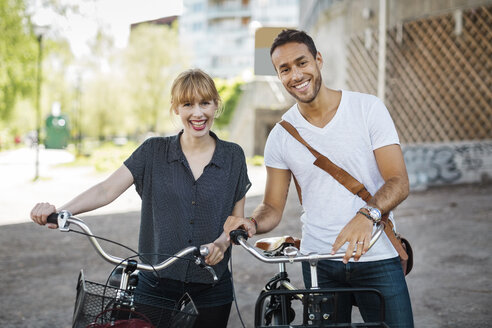 Portrait of happy business people with bicycles standing on city street - MASF04115