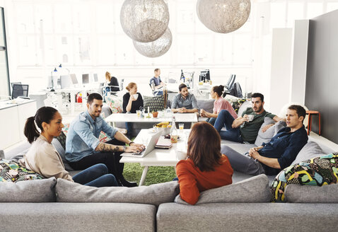 Multi-ethnic business people having discussion in modern office lobby - MASF04133
