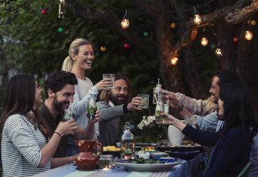 Multi-ethnic friends toasting drinks at dinner table in yard - MASF04136