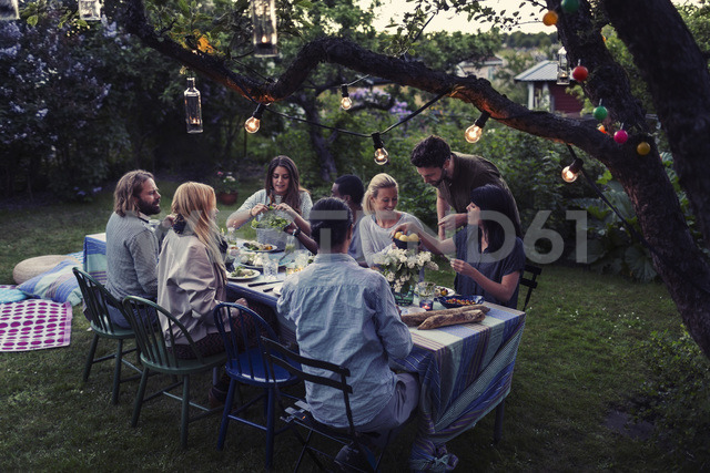 Multi-ethnic friends having food at dining table in yard - MASF04139 - Maskot ./Westend61