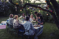 Multi-ethnic friends having food at dining table in yard - MASF04139