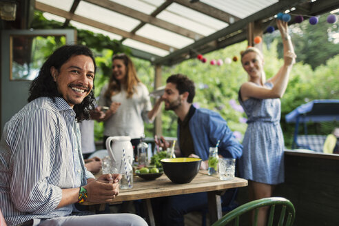 Portrait of happy man sitting at table while enjoying party with friends at summer house - MASF04142
