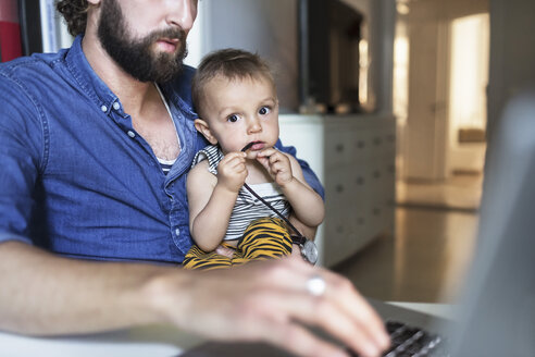 Portrait of baby boy with father using laptop at home - MASF04145