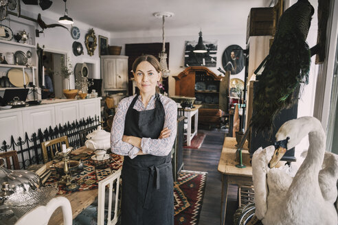 Portrait of female retailer with arms crossed standing in antique shop - MASF04157
