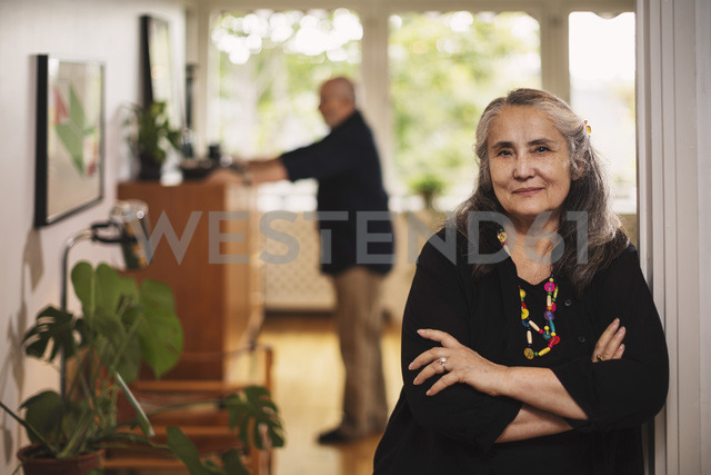 Portrait of confident senior woman standing with man in background at home - MASF04160