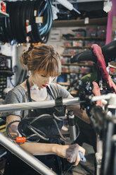 Mid adult mechanic repairing bicycle in workshop - MASF04163