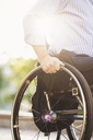 Midsection of man sitting in wheelchair on sunny day outdoors - MASF04169