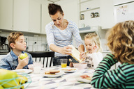 Mother serving breakfast to children at dining table in kitchen - MASF04178
