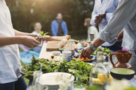 Midsection of friends preparing food at dining table in backyard - MASF04187