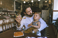 Mid adult man feeding baby boy at restaurant table - MASF04190