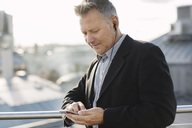 Mature businessman listening music through phone while standing at office - MASF04208