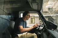 Mature man looking away while driving food truck - MASF04214