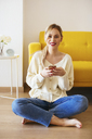 Blonde woman using smartphone at home - EBSF02407