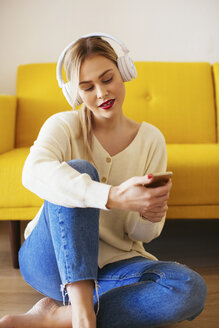 Blonde woman with headphones using smartphone at home - EBSF02410