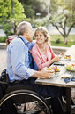 Happy mature couple looking at each other while having food in yard - MASF04216