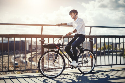 Happy businessman with bicycle on bridge in city - MASF04219