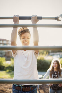 Happy teenager hanging from monkey bars at park - MASF04237