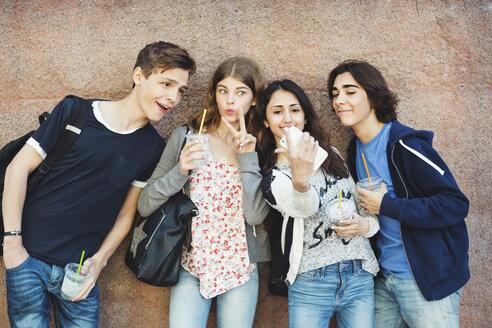 Happy teenagers gesturing while taking selfie against wall - MASF04240