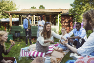 Happy woman serving pizza to friends in backyard during summer party - MASF04246