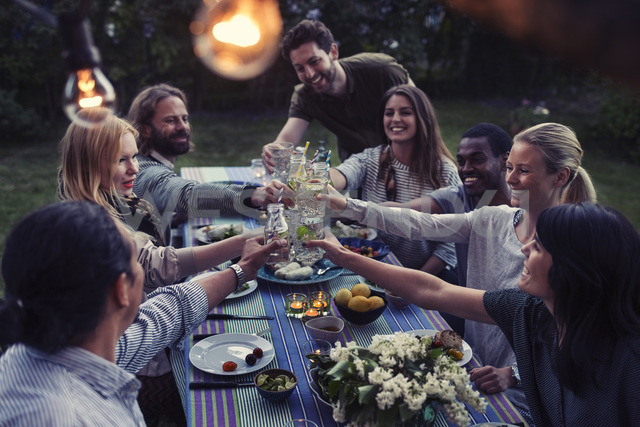 Happy multi-ethnic friends toasting drinks at dinner table in yard - MASF04249
