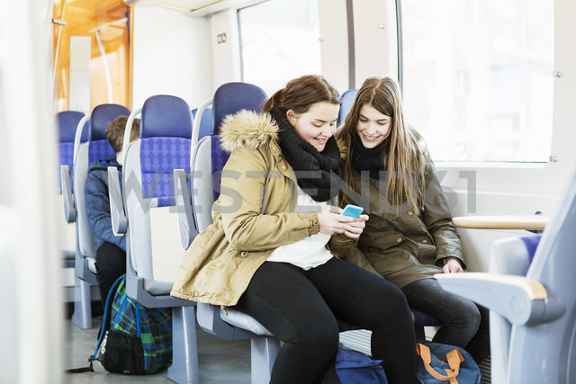 Happy young female friends using mobile phone while traveling in train - MASF04255