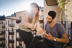 Happy couple using smart phone while reading guidebook on balcony - MASF04258