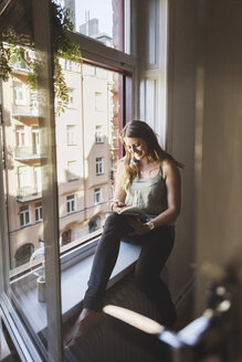 Happy woman using smart phone while holding guidebook on window sill at home - MASF04261