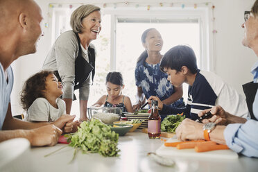 Happy multi-ethnic family preparing Asian food at kitchen - MASF04264