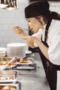 Kvinnlig kock smakar av i restaurangkök - MASF04276