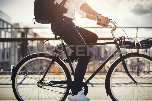 Low section of businessman riding bicycle on bridge - MASF04285