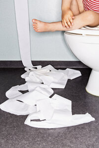 Low section of girl sitting on toilet bowl with paper on floor - MASF04288
