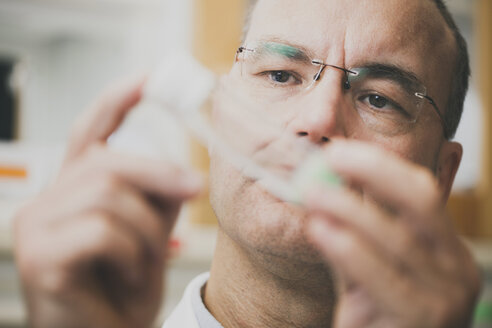Male scientist examining sample in test tube at laboratory - MASF04309