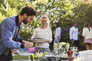 Happy young woman holding plates while enjoying summer party with friends in yard - MASF04315