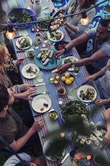High angle view of friends having food at dining table in yard - MASF04318