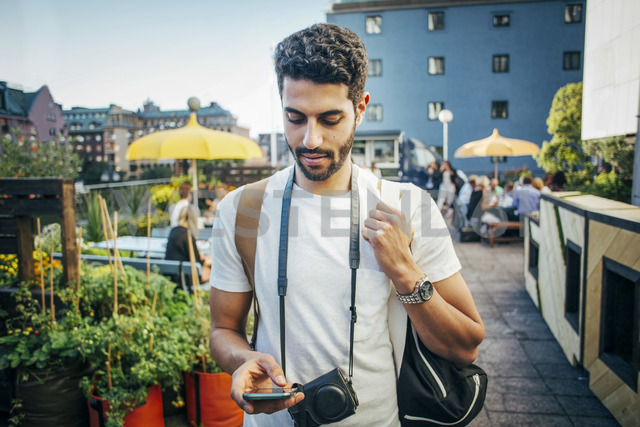 Male tourist using smart phone in city - MASF04324