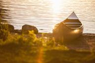 Canoe moored on lakeshore during sunset - MASF04342