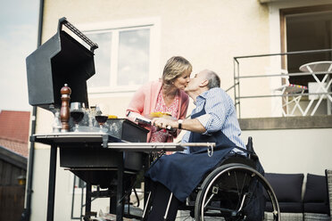 Disabled man in wheelchair kissing woman while barbecuing at yard - MASF04348