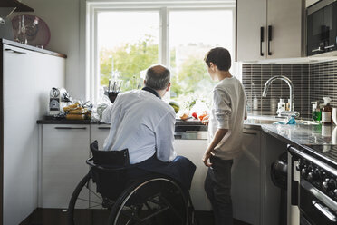 Disabled father preparing food son in kitchen - MASF04351