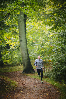 Confident man running in forest - MASF04360