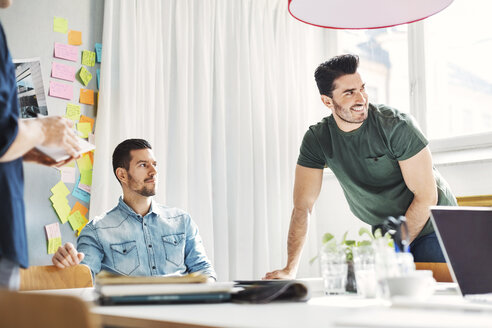 Confident business people at desk during meeting in office - MASF04369