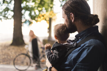 Father at door holding baby boy while looking at woman leaving for work - MASF04378