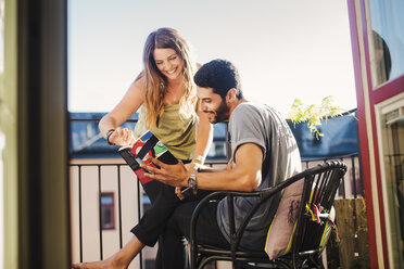 Couple reading guidebook together on balcony - MASF04381