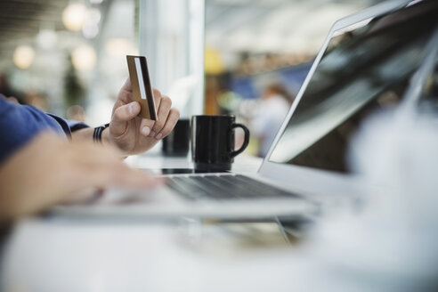 Cropped image of businessman using credit card and laptop at airport lobby - MASF04384